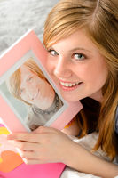 Teenage girl holding picture of her love