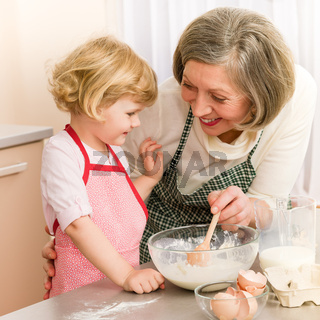 Child girl and grandmother baking cake