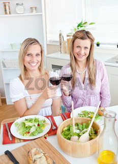 Beautiful women clinking glasses and eating salad sitting in the kitchen