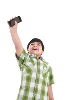 boy holding up cellular phone and smiling