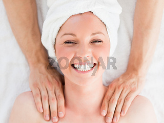 Closeup of a charming red-haired woman receiving a massage in a spa centre