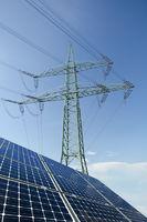 Solarmodule und Strommast mit Leitungen