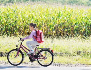 schoolgirl traveling to school on bicycle