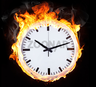 Clock in fire on black background