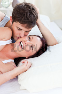 Cheerful caucasian couple lying on bed