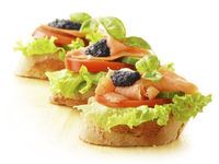 Three sandwiches with salmon and caviar