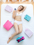 Good-looking woman lying in bed with shopping bags