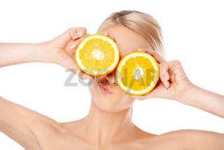 Blond woman making glasses with orange halfs
