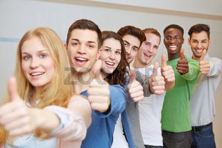 Jubelnde Studenten halten Daumen hoch
