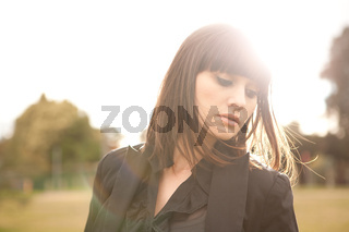 Young caucasian woman in a park with soft summer light