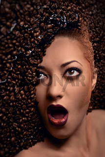 Gorgeous woman's face over coffee beans