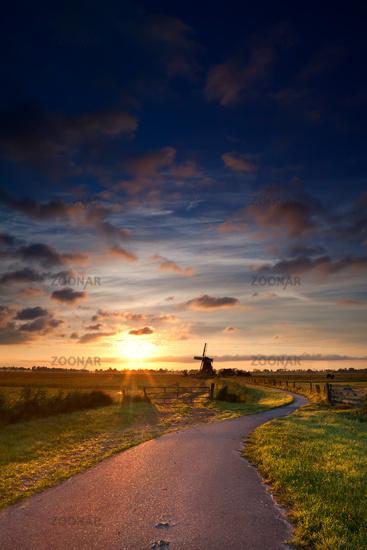 warm summer sunrise and windmill