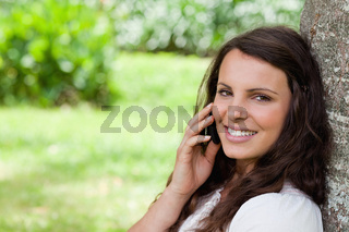 Young smiling woman talking on the phone while looking at the camera