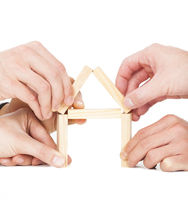 businessman's hand building house by wooden block