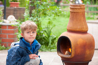Boy sitting in front of a garden oven