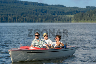 Young men sitting in motorboat scenic landscape