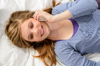 Girl lying in bed talking on phone