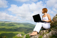 woman sitting on  edge of a cliff with a laptop