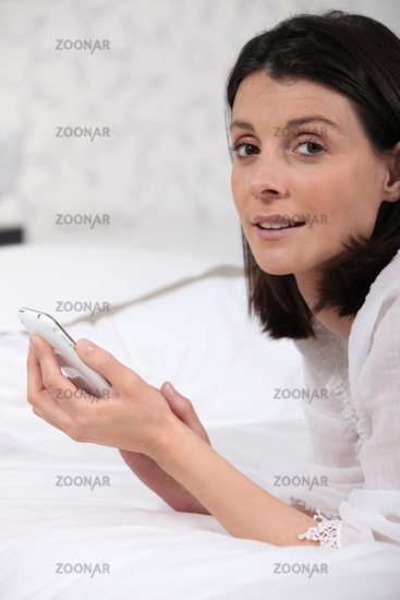 Woman laid on a bed sending text message