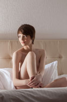 Attractive naked woman in hotel bed