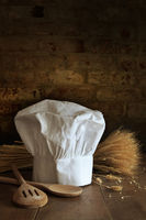 Chef hat and spoons with brick background