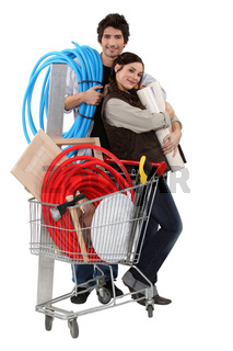Couple with trolley full of supplies