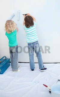 Siblings painting a wall