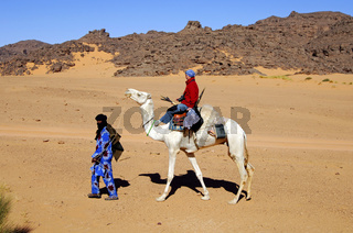 Tuareg führt eine Touristin durch die Wüste