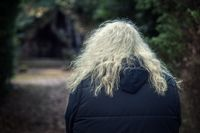 a human being with long blonde curly hair in rear