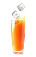 Ice cubes falling in glass of orange juice