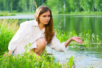 Young woman relaxing on the shore of lake