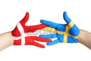 two hands painted in the colors of denmark and sweden shaking