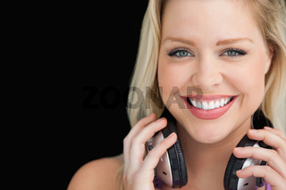 Smiling woman standing while holding her headphones