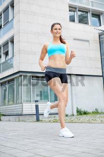 Sportliche Frau beim Laufen in der Stadt