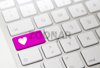 White computer keyboard with pink 'heart' button