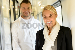 Woman and man smiling standing in train