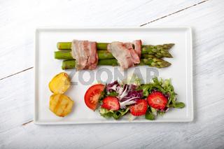 Gegrillter Spargel mit Speck auf einem Teller