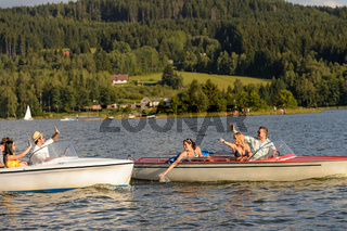 Young friends having fun in motorboats