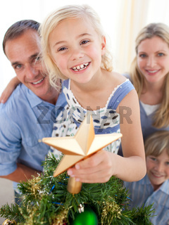 Father lifting his daughter to put the Christmas star on top of the tree