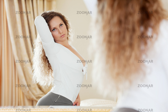 Beautiful woman looking in the mirror