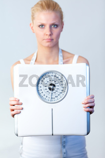 Serious woman holding a scales with focus on scales