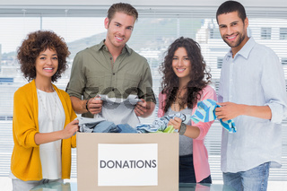 Smiling team of volunteers taking out clothes from a donation box