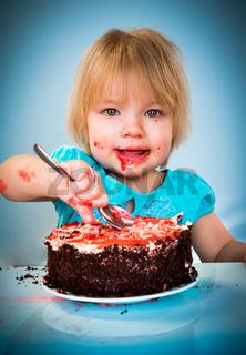 Little baby girl eating cake
