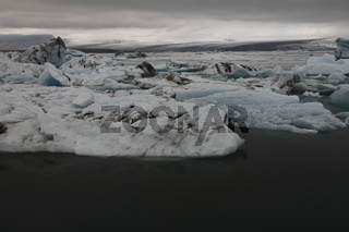 Icebergs in Jökulsárlón. Jökulsárlón Glacier Lagoon is a lagoon formed in front of the Breiðamerkurjökull glacier in South-East Iceland. Portions of the glacier break off its leading edge forming icebergs that float in the lagoon. Breiðamerkurjökull (Brei