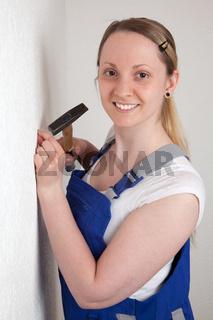 Junge Frau mit Hammer und Nagel