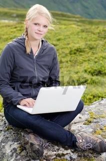 junge blonde Frau mit Laptop auf Stein vor Berglandschaft