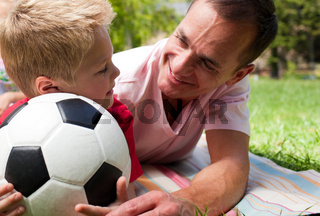 Close-up of an attentive father and his son holding a soccer ball