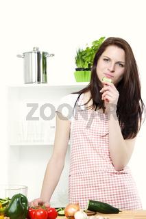 junge frau in der küche knabbert an einer gurke
