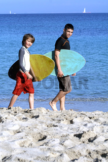 healthy fit active child with surf instructor or teacher on beach summer vacation