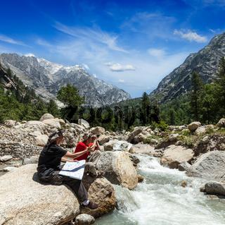 Hiker trekkers read a trekking map on trek in Himalayas mountains. Himachal Pradesh
